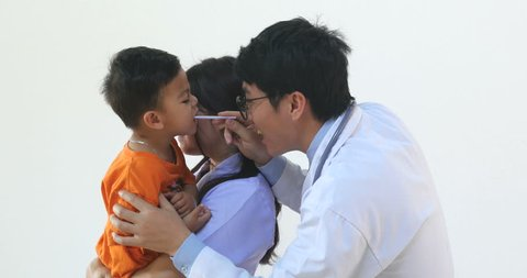 Doctor Man Examining Mouth Of Little Boy