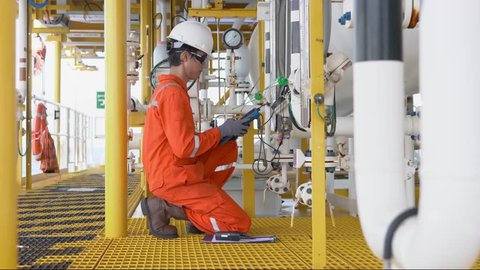 Electrical and instrument operator calibrate level transmitter at offshore oil and gas wellhead remote platform, Onsite service worker.