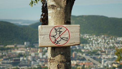 A tablet with a picture of a crossed witch on a broomstick. A sign forbidding witches to fly. In the background, the city of Bergen in Norway