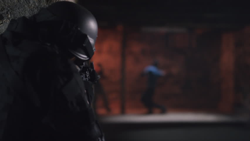 Member of SWAT team patrolling a dark warehouse and shooting criminals with a rifle. Close up. Shot with a RED camera. 4k footage.