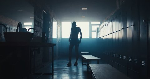 DOLLY IN Caucasian female athlete taking off shirt in a gym locker room, angry, not satisfied with her workout results. 4K UHD 60 FPS SLOW MOTION