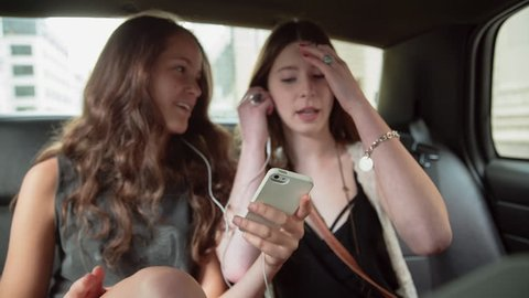 Driving shot of happy female friends listening music and paying currency while traveling in taxi