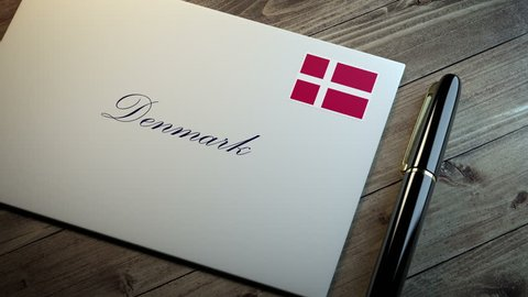Country name written on a card or envelope in cursive font with a sleek pen on a wooden table surface under beautiful classy light. Stamp in the corner shows the flag of Denmark