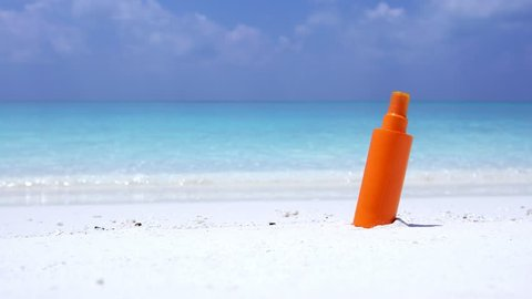 Sunscreen protection cream on white sand against turquoise sea water. Tropical summer vacation concept