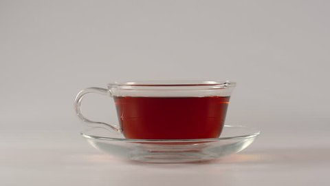 Drinking of black tea from a teacup on a white background - Stop motion