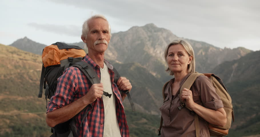 Positive old caucasian couple trekking in mountains with backpacks, enjoying their adventure - portrait shot 4k #1015182991