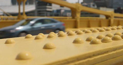 A slow dolly tracking shot of the yellow steel beams on the Andy Warhol Bridge over the Allegheny River in Pittsburgh as traffic passes by.