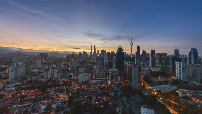 Time lapse: Beautiful and dramatic sunrise view of the Kuala Lumpur skyline and Malaysia national landmarks from night to day at dawn. High Quality 4K.