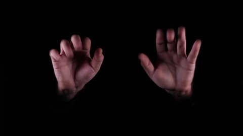 Hand Gestures coming out of the dark into the light. Holding GFX object. The number ten.