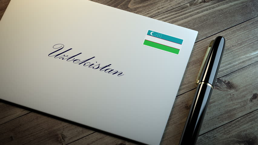 Country name written on a card or envelope in cursive font with a sleek pen on a wooden table surface under beautiful classy light. Stamp in the corner shows the flag of Uzbekistan