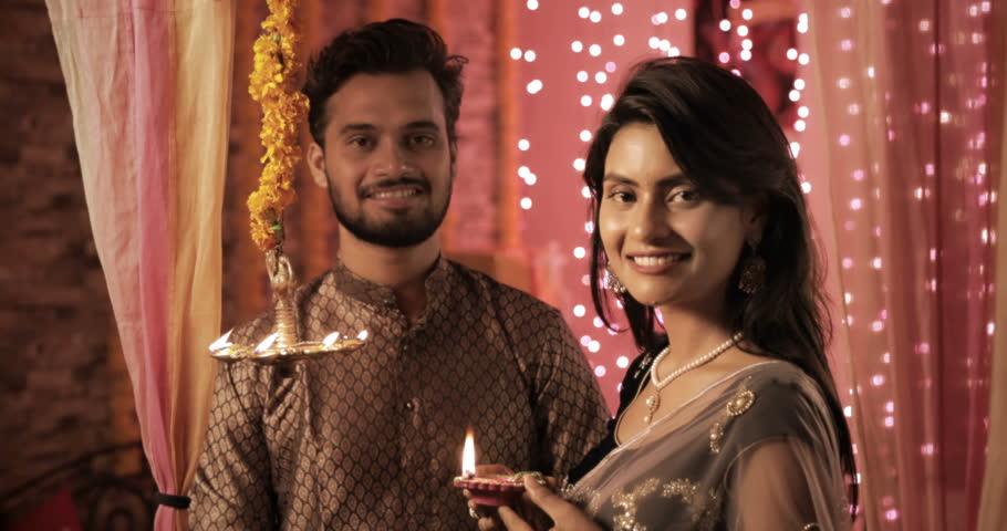 Newly wed bride and groom in a house interior decorated with lights and flowers. A attractive woman wearing sari lights a oil lamp during Diwali festival while man wearing Kurta looks on with a smile