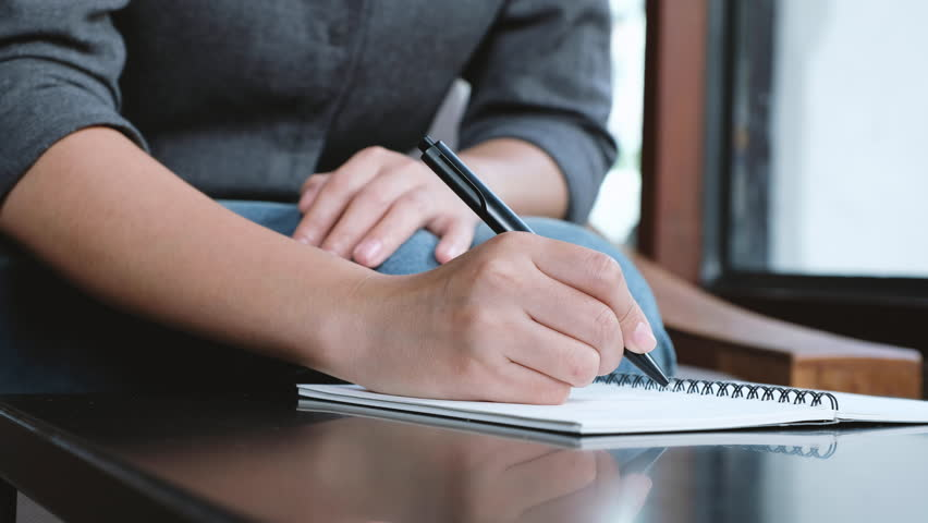 A woman's hand writing down on a white blank notebook on table