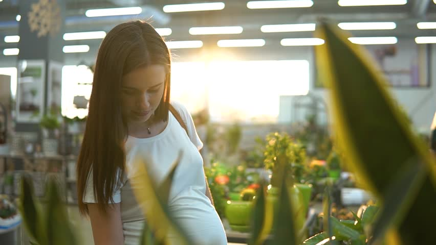 Beautiful girl in a white T-shirt buying green flower plants at flower shop. | Shutterstock HD Video #1015247581