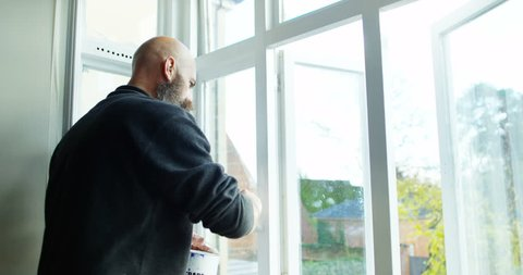 4K Mature hipster man redecorating at home, painting interior window frames. Slow motion.