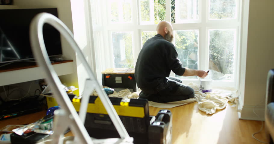 4K Man painting home interior window frames, surrounded by tools & equipment. Slow motion.