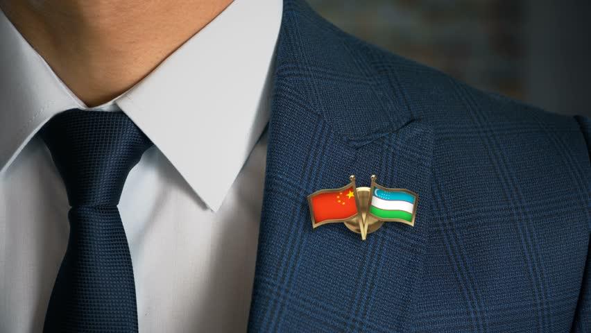 Businessman Walking Towards Camera With Friend Country Flags Pin China - Uzbekistan