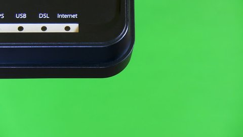 Close up of router and modem in one isolated on green background. PC peripheral device's lights blinking while it is connecting to internet, copy space.