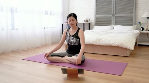 Asian woman doing the meditation following the instruction on the digital pad.