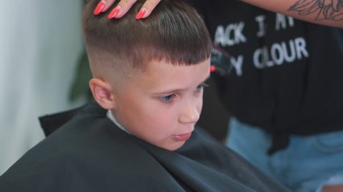 Cheerful Boy Smiling While Sitting In Chair And Getting His Hair Cut