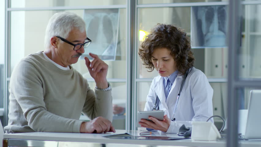 Beautiful female practitioner sitting at desk in modern doctor office with glass walls and discussing something on digital tablet with senior male patient | Shutterstock HD Video #1015339531