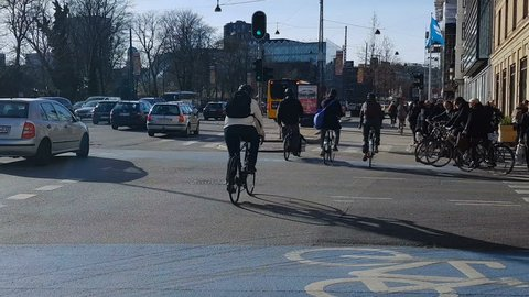 COPENHAGEN, DENMARK - CIRCA APRIL 2018: People in the city. Copenhagen citizens going work by cars and bicycles, rush hour on crowded street