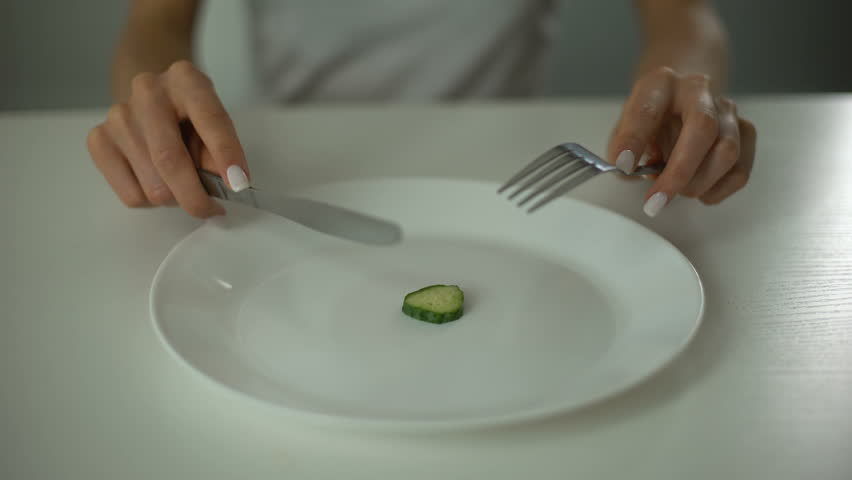 Girl slicing cucumber, obsessed with undereating, fear of overweight, anorexia | Shutterstock HD Video #1015350511