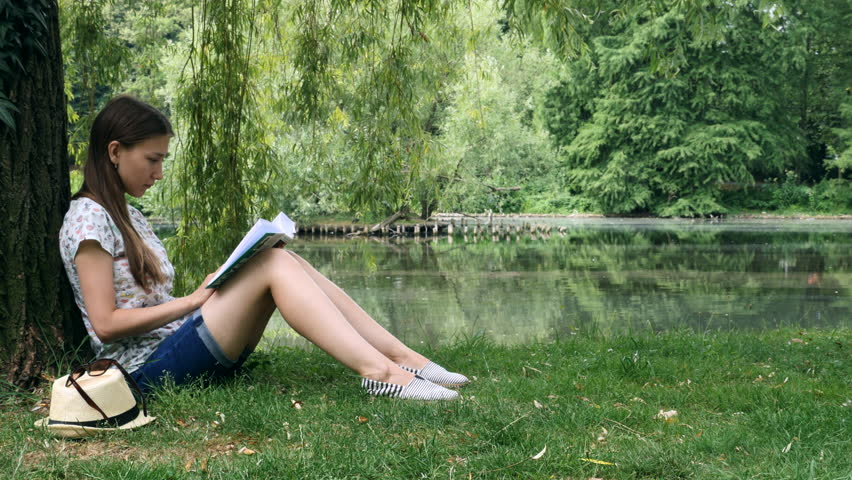 Girl sitting in the park near the lake under the tree and reading a book.