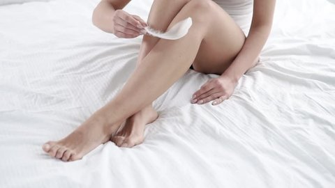Skin Care. Woman Touching Leg With Feather Sitting On Bed