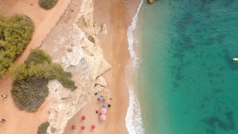 Drone shot of a beach with parasols in Algarve, Portugal. PANING TOP TO BOTTOM