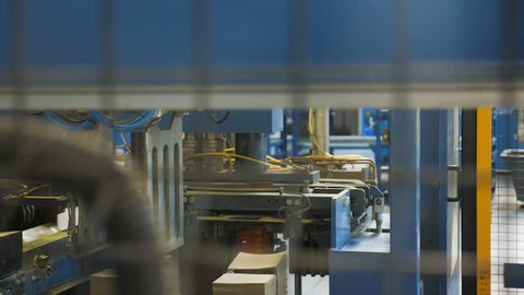 View through metal grid mechanical arm transports paper stacks for galvanic battery manufacturing