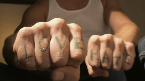 Man showing LOVE and HATE tattoo letters on hands closeup