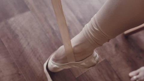 Close-up of ballerina's legs with pointe shoes. Dancer wears ballet slippers. Prepare for the dance. Interior studio in the old style. Natural lighting with haze