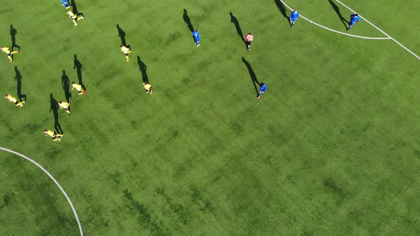 Aerial football match play. Aerial shot Two teams playing ball in football outdoors, top view. Football game outdoors, green field with markings, players running around with a ball