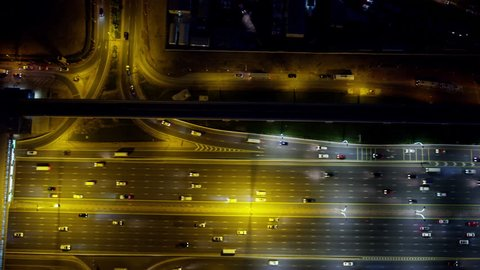Aerial night overhead illuminated view city highway commuter vehicle traffic metro rail commercial area modern vehicle transport system UAE Middle East Dubai RED WEAPON
