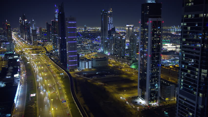 Dubai - March 2018: Aerial night illuminated city view Sheikh Zayed road skyline skyscrapers commercial condominiums vehicle transport highway metro UAE RED WEAPON #1015444141