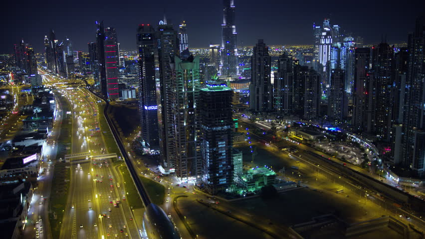 Dubai - March 2018: Aerial night illuminated city view Sheikh Zayed road skyline skyscrapers commercial condominiums suburbs vehicle transport highway metro UAE Dubai RED WEAPON #1015444651