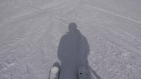 Shot in movement skis and shadow of skier on snow ski slope, quickly rolls downhill skiing in winter at the resort, slow motion, hd