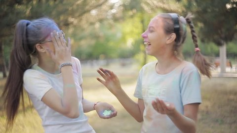 Two girls on the festival of colors Holly blow each other colored powder
