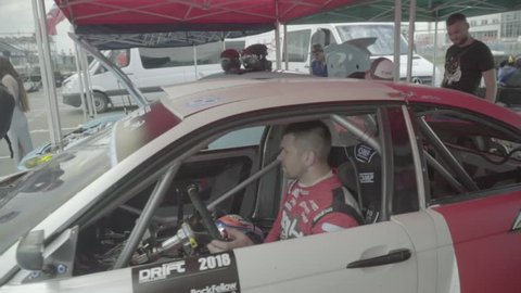 KYIV, UKRAINE – JUNE 29, 2018. Driver racer in a racing car before the race. Slow motion