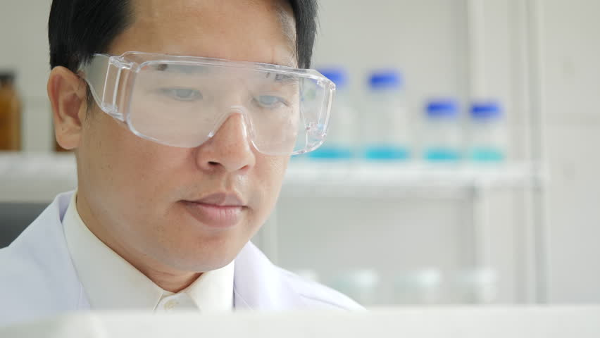 Close-up of a Medical research scientist takes out petri dish with frozen samples of cells from a cryogenic nitrogen container in a science research lab. He works in a busy modern laboratory center.