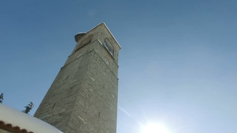 Hypertimelapse of church bell tower against blue sky