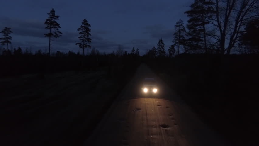 Aerial drone tracking shot of a 4x4 driving in night on a gravel road