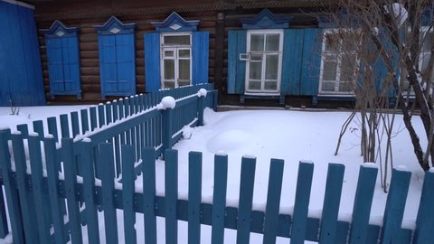 Cold Siberian winter wooden old house fence yard. Unique authentic Russian style wood carving architecture. Irkutsk center tourist attraction. White snow wind blizzard. Gimbal professional 4k