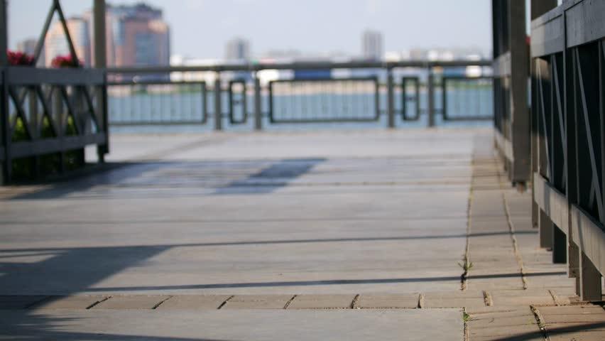 A beautiful slender girl rides a skateboard along the embankment on a summer sunny evening | Shutterstock HD Video #1015565311