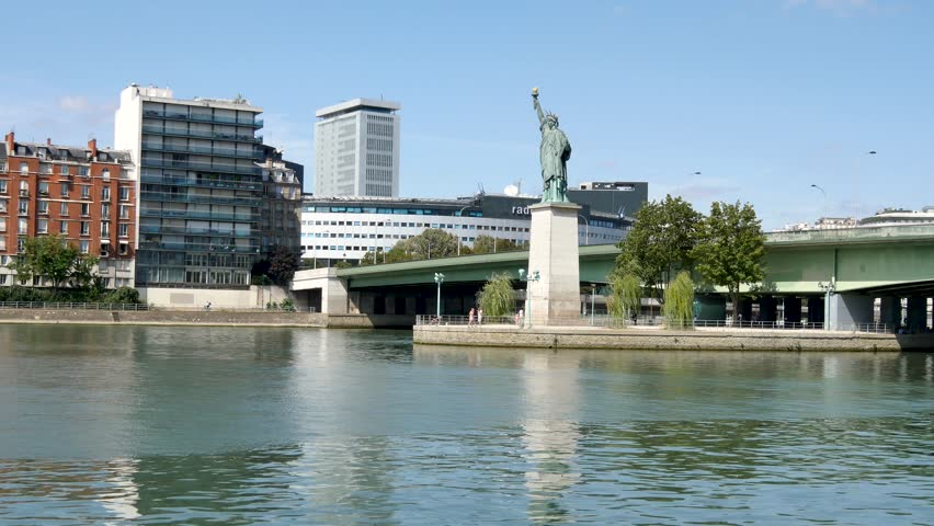 Statue of Liberty in Paris. The statue is smaller than the one in New York. It is located on a small island in the Seine. Front view. Pont de grenelle (parisian bridge) behind the statue. | Shutterstock HD Video #1015615591