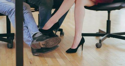 2f69fe1d7eb Close-up of female legs caressing man's legs under table. female secretary  flirting with her boss touching his legs under desktop. 4k