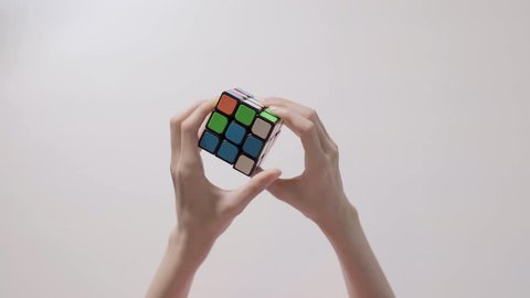 TAIPEI, TAIWAN - AUGUST 21, 2018: Child's hands solving rubik's cube puzzle. Puzzle cube, puzzle game, best-selling toys. Child's hands closeup. Part 01. Recycled video.