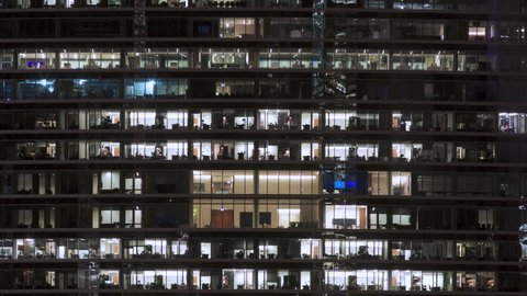 Timelapse at night of a modern office building with glass windows and lights going on and off