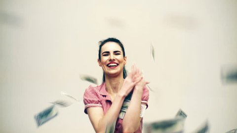 Smiling girl under a money rain catches money isolated on white background. Money rain concept