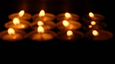 Blurred lit tealights candles in the dark.